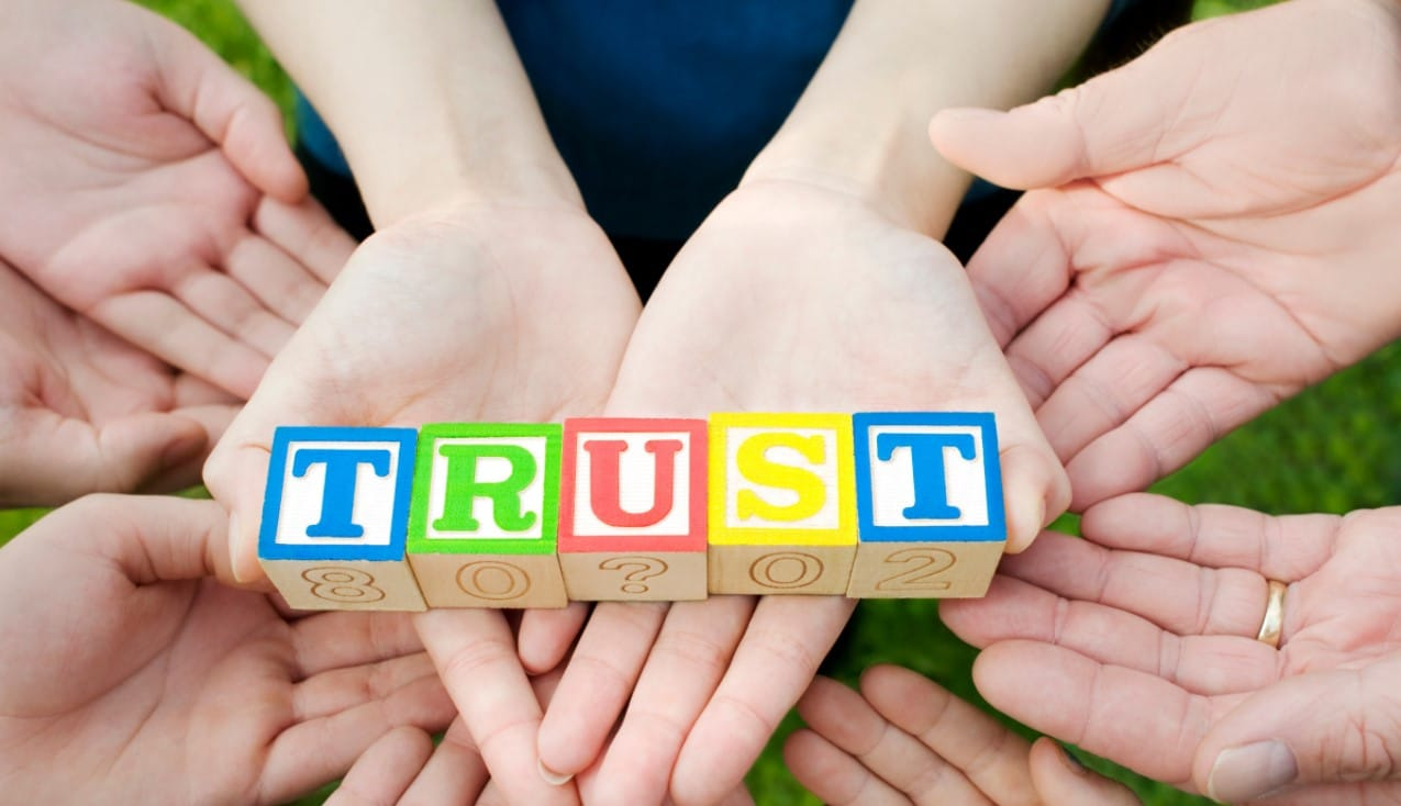 Charitable Lead Trust: Several hands holding colored blocks that spell trust